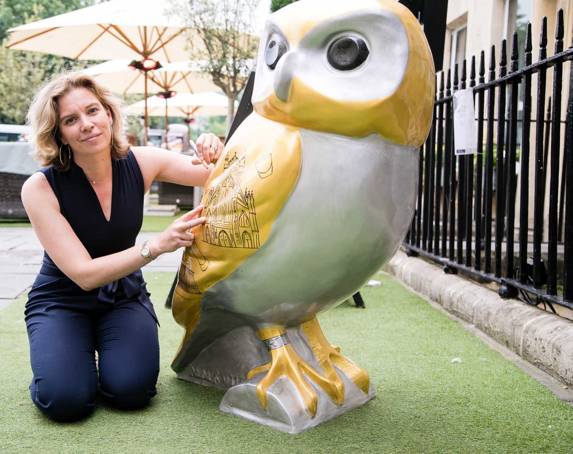 Emma Taylor outside The Abbey Hotel signing her painted artwork owl, Artis